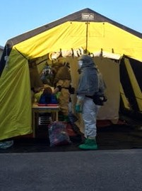 Sept 22-23, 2015 51st Civil Support Team Hazmat Exercise. Responders in hazmat suits caring for patient under hazmat tent.